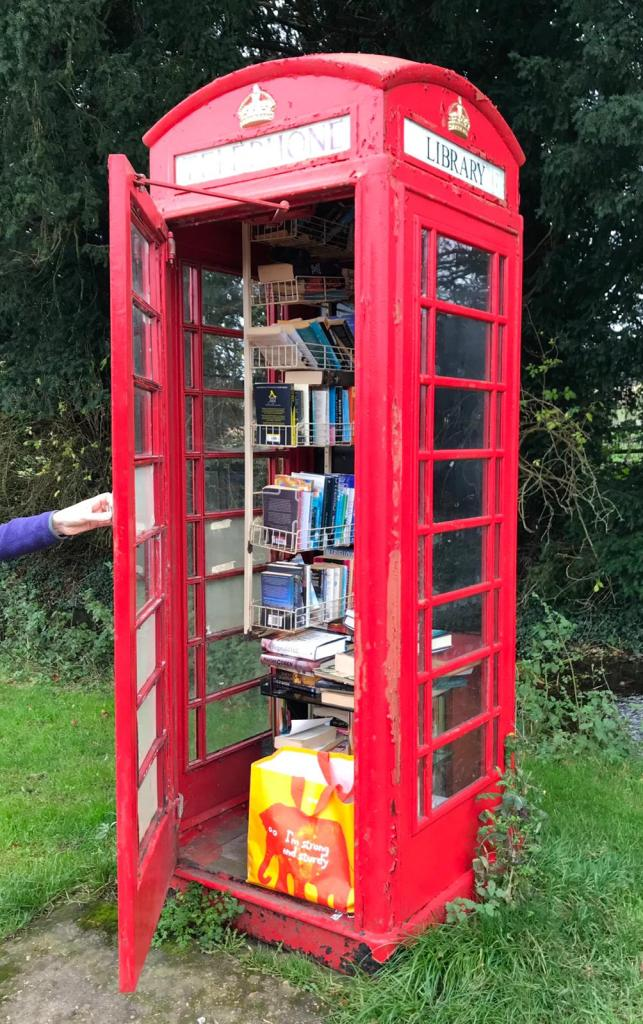 A phone box full of books with Libray on the sign